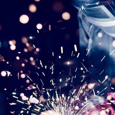Employee welding steel with sparks, using MiG MAG welder